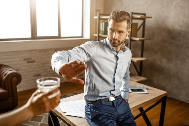 Young handsome businessman lean to table in his own office. he show stop sign to human holding glass of whiskey. guy refuse.