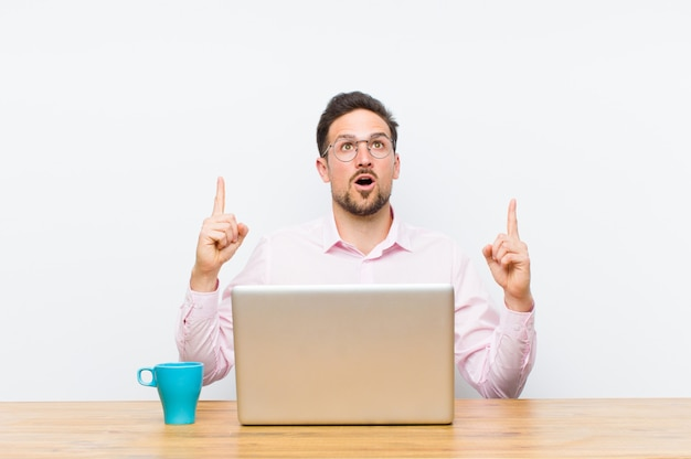 Young handsome businessman looking shocked, amazed and open mouthed, pointing upwards with both hands to copy space