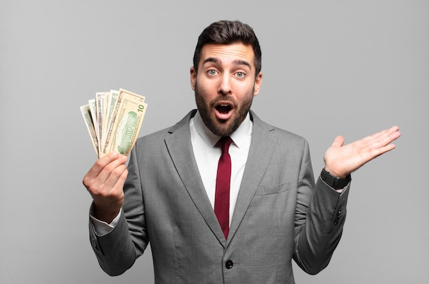 Young handsome businessman looking surprised and shocked, with jaw dropped holding an object with an open hand on the side. bills or money concept