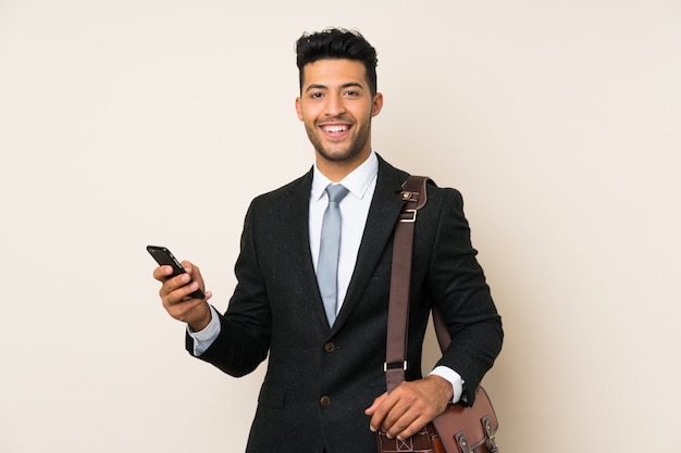 Young handsome businessman man over isolated wall