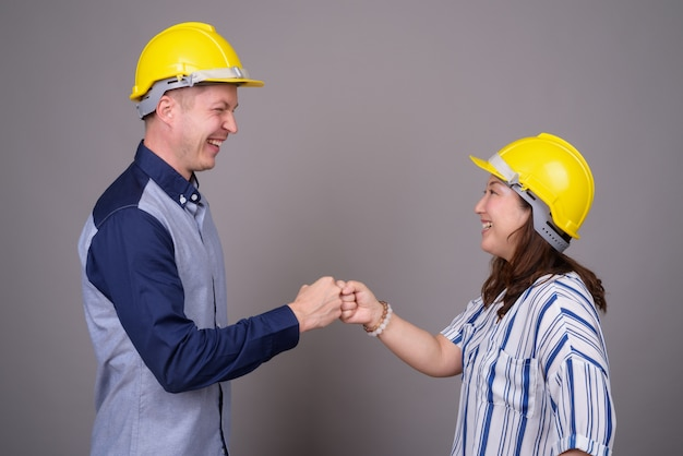 Young handsome businessman and mature asian businesswoman wearing hardhat
