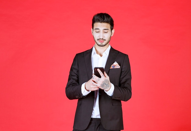 Young handsome businessman messaging with someone over red