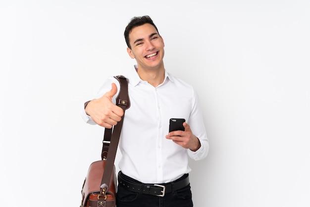 Молодой красивый бизнесмен на стене с большими пальцами руки вверх