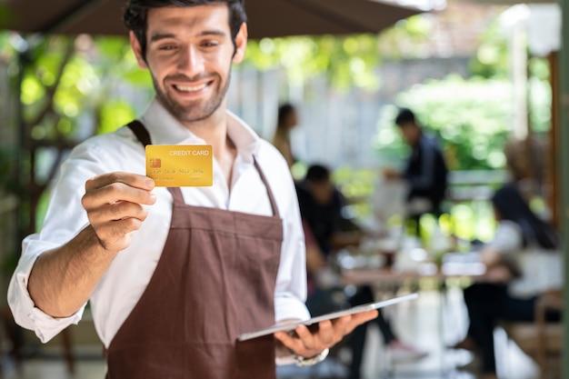若いハンサムなビジネスマンはコーヒーショップを所有しており、タブレットとクレジットカードを持って、すべてのサービスの現金支払いを顧客に伝えています