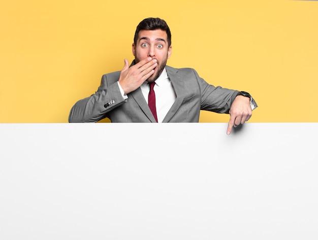 Молодой красивый бизнесмен, указывая или показывая пустое место для yout концепции