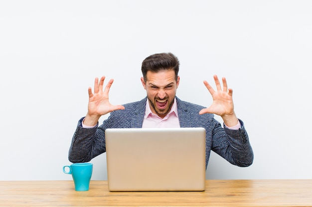 Young handsome businessman screaming in panic or anger, shocked, terrified or furious, with hands next to head