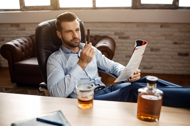 Young handsome businessman sit on chair and look at cigar in his own office. he hold legs on table and journal in hands. glass and graphene of whiskey.