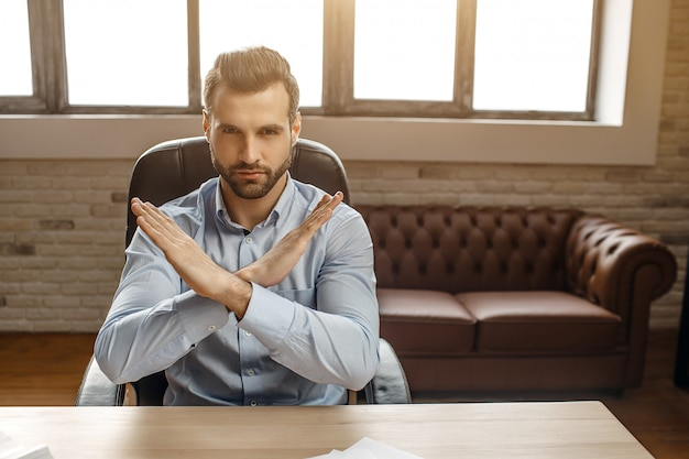 Young handsome businessman sit at table in his own office. he hold hands crossed in forbidden sign. angry and very serious.