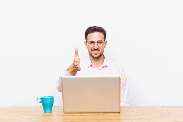 笑みを浮かべて、あなたに挨拶し、成功した取引、協力の概念を閉じるために手を振るを提供する若いハンサムな実業家