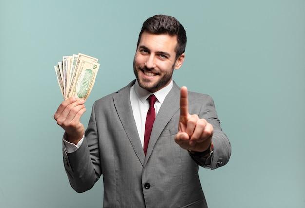 誇らしげに、自信を持って笑顔でナンバーワンのポーズをとる若いハンサムなビジネスマンは、リーダーのように感じます。手形またはお金の概念