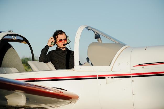 Молодой красивый бизнесмен, стоящий внутри частного самолета