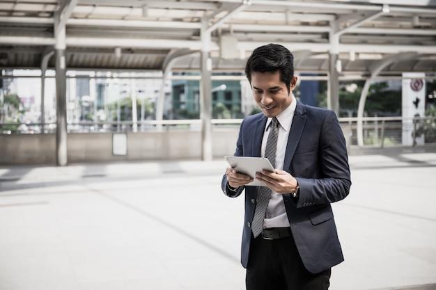 Молодой красивый бизнесмен, используя его тачпад, стоя в бизнес-центре.