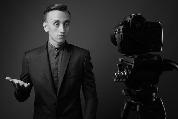 若いハンサムなビジネスマンは灰色の壁に向かってビデオブログ。黒と白