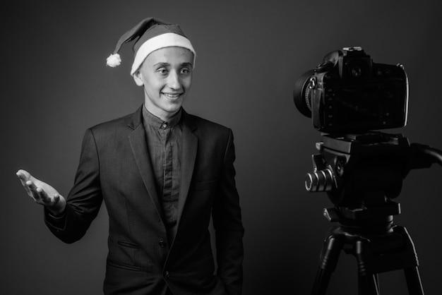 若いハンサムなビジネスマンは、灰色の壁に対してクリスマスの準備ができています。黒と白