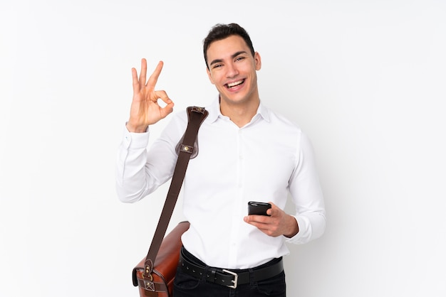 Young handsome businessman on wall surprised and showing ok sign