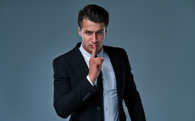 Young handsome businessman wearing elegant suit standing over isolated gray background asking to be quiet with finger on lips. silence and secret concept.