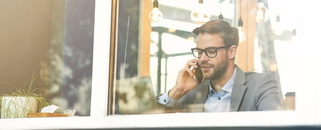 카페에서 원격으로 일하는 동안 안경을 쓰고 통화하는 젊은 미남 사업가