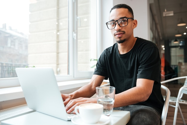 Young handsome businessman wearing glasses sitting near window and typing by laptop computer