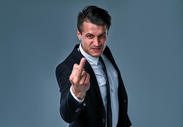 양복과 넥타이를 착용하고 고립된 회색 배경 위에 서 있는 젊고 잘생긴 사업가 가운데 손가락, 무례하고 무례한 표정을 보여줍니다.