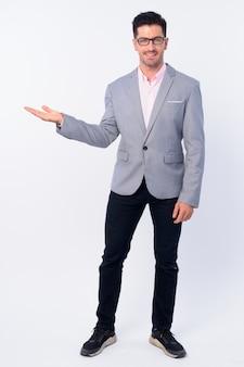 흰 벽에 고립 된 양복을 입고 젊은 잘 생긴 사업가