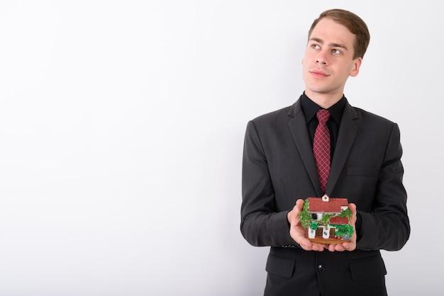 Костюм молодого красивого бизнесмена нося на белой стене