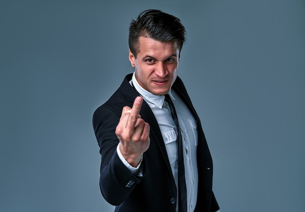 Young handsome businessman wearing suit and tie standing over isolated gray background showing middle finger, impolite and rude fuck off expression.