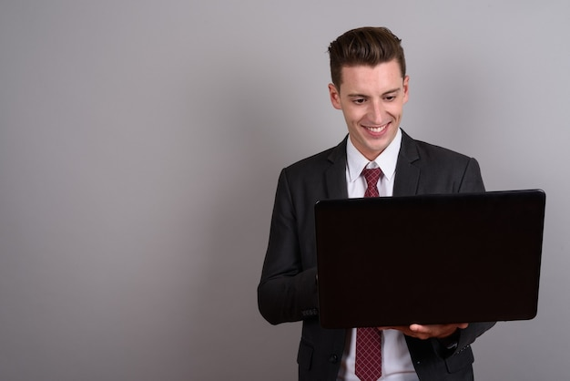 Young handsome businessman wearing suit while holding laptop on gray