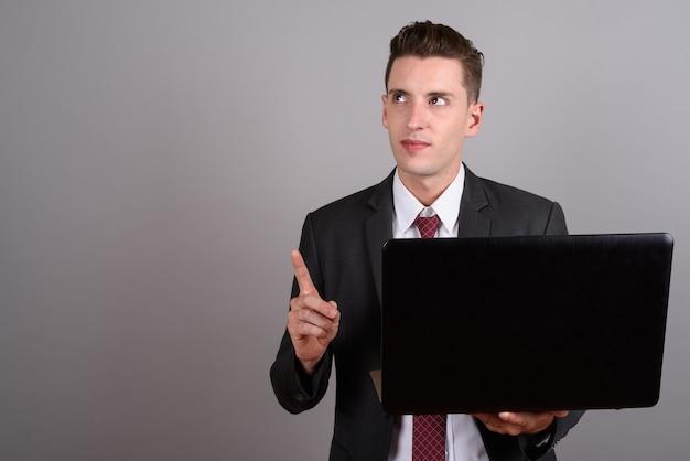 灰色のラップトップを保持しながらスーツを着て若いハンサムな実業家