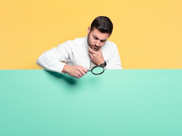 虫眼鏡で若いハンサムなビジネスマン。検索コンセプト