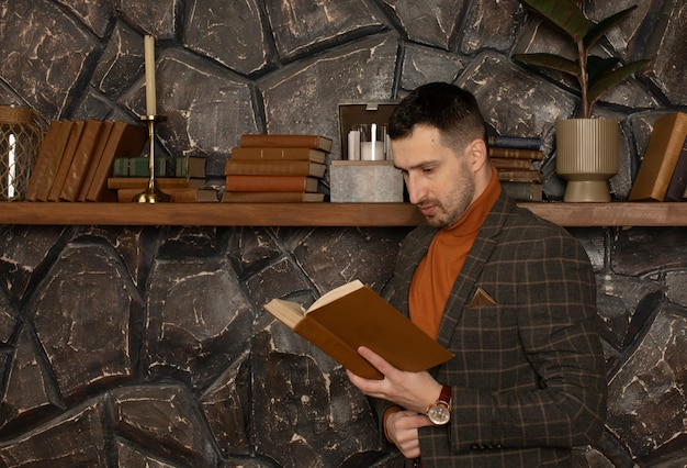 Young handsome businessman with beard in suit reading book