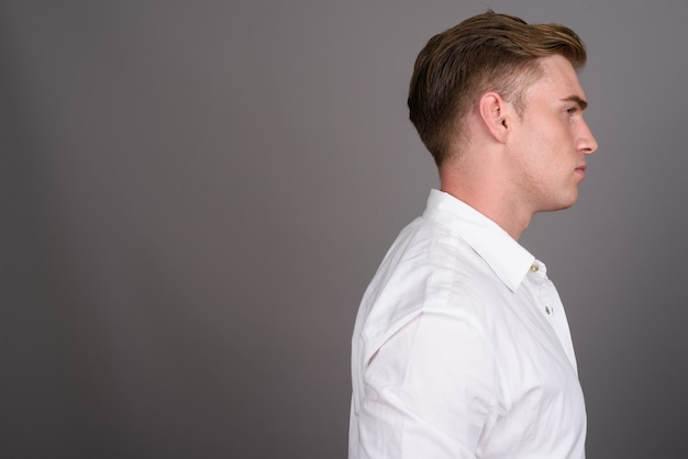 Young handsome businessman with blond hair on grey wall