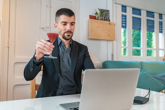 Young handsome businessman with a cocktail drink in a video call online