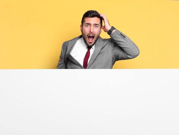 灰色のプラカードを持つ若いハンサムなビジネスマン