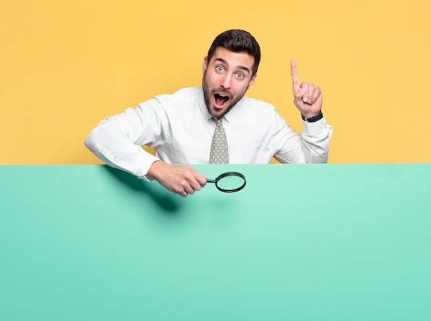 Young handsome businessman with a magnifying glass. search concept
