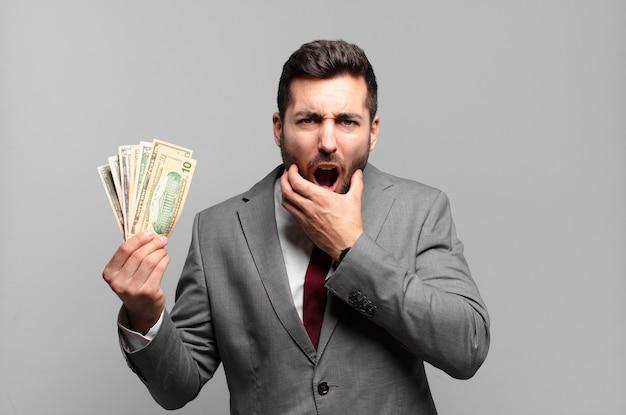 입과 눈을 크게 벌리고 턱에 손을 대고 젊은 잘 생긴 사업가, 불쾌하게 충격을 받고 무엇을 말하거나 와우