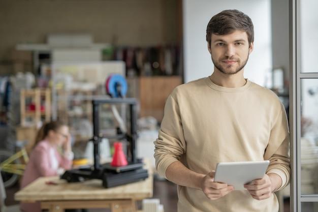 Молодой красивый бизнесмен с планшетным компьютером, серфингом в сети для творческих веб-сайтов с коллегой на 3d-принтере