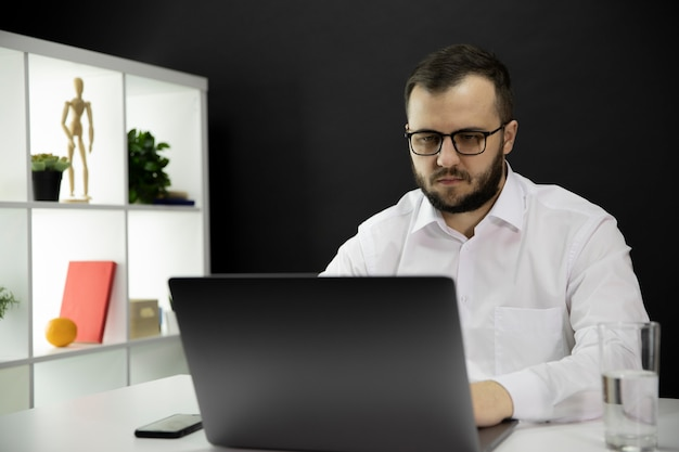 Young handsome businessman working at computer in home office, makes video call