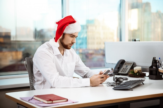 Young handsome businessman working in office on christmas day.