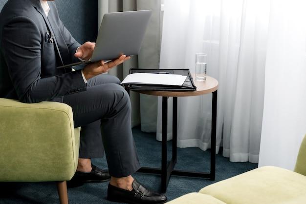 ホテルの部屋でラップトップで働く若いハンサムなビジネスマン