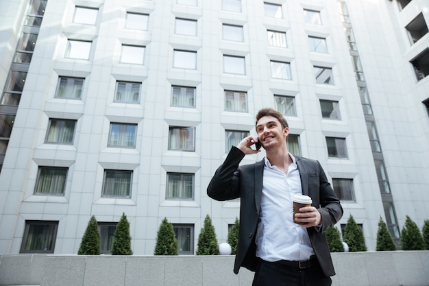 Молодой красивый занятой человек разговаривает по телефону в бизнес-центре
