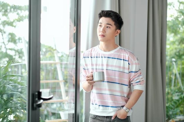 Молодой красивый беззаботный мужчина возле современного окна в полный рост, наслаждаясь чашкой кофе, глядя на улицу