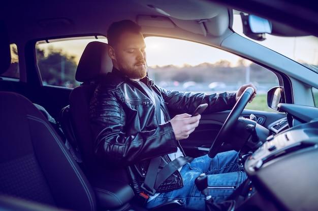 若いハンサムな白人彼の車を運転してスマートフォンを使用しての革のジャケットの金髪の男を生やした。