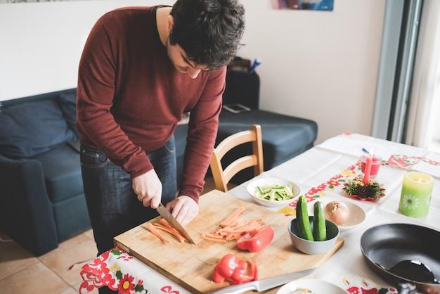 Молодой красивый кавказских каштановых волос человек, резки некоторые морковь с ножом на разделочную доску, вокруг чаши, овощи, кастрюлю и нож - здоровые, veggie, концепция питания