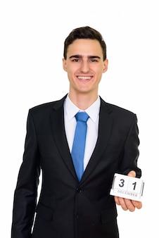 白で隔離12月31日カレンダーを保持している若いハンサムな白人実業家