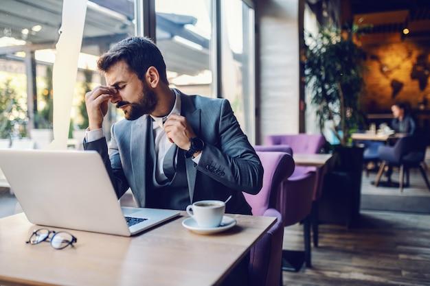 カフェに座って、頭痛と不快感を持っているスーツの若いハンサムな白人実業家。テーブルの上にはノートパソコンとコーヒーがあります。