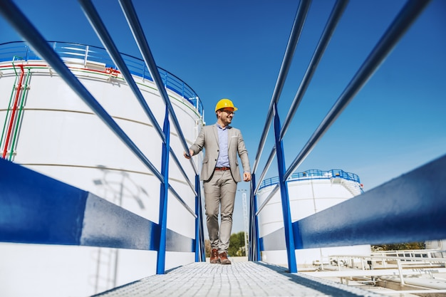 Young handsome caucasian businessman in suit and with helmet on head walking on bridge and looking at his refinery.