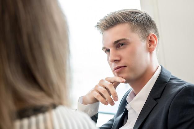 Молодой красивый кавказский бизнесмен думая с рукой на подбородке