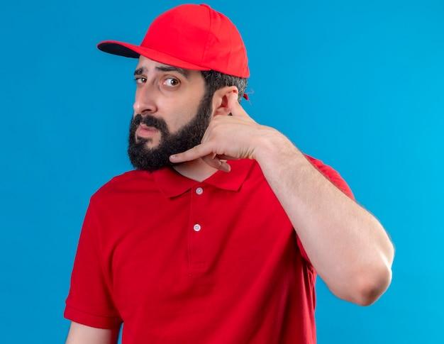 赤い制服と帽子を身に着けている若いハンサムな白人配達人がカメラを見て、青い背景で隔離の呼び出しジェスチャーを行う