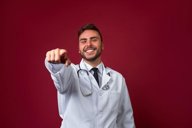 Молодой красивый кавказский доктор на красной предпосылке