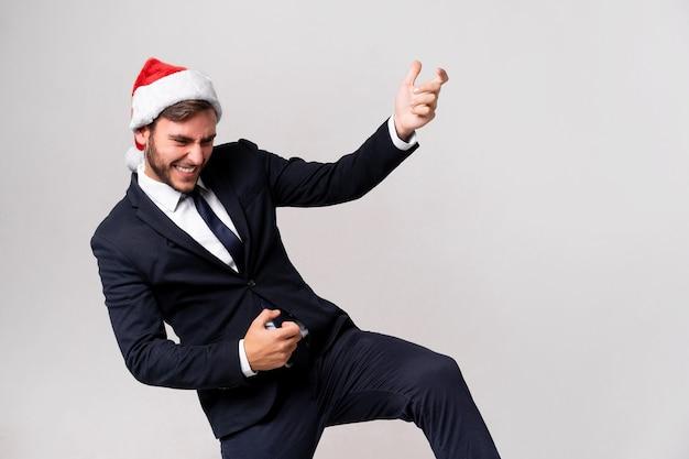 Молодой красивый кавказский парень в деловом костюме и шляпе санты